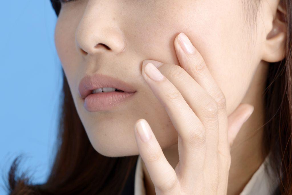 肌荒れを心配する女性の画像