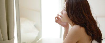 鏡の前で女性が肌を見ている画像