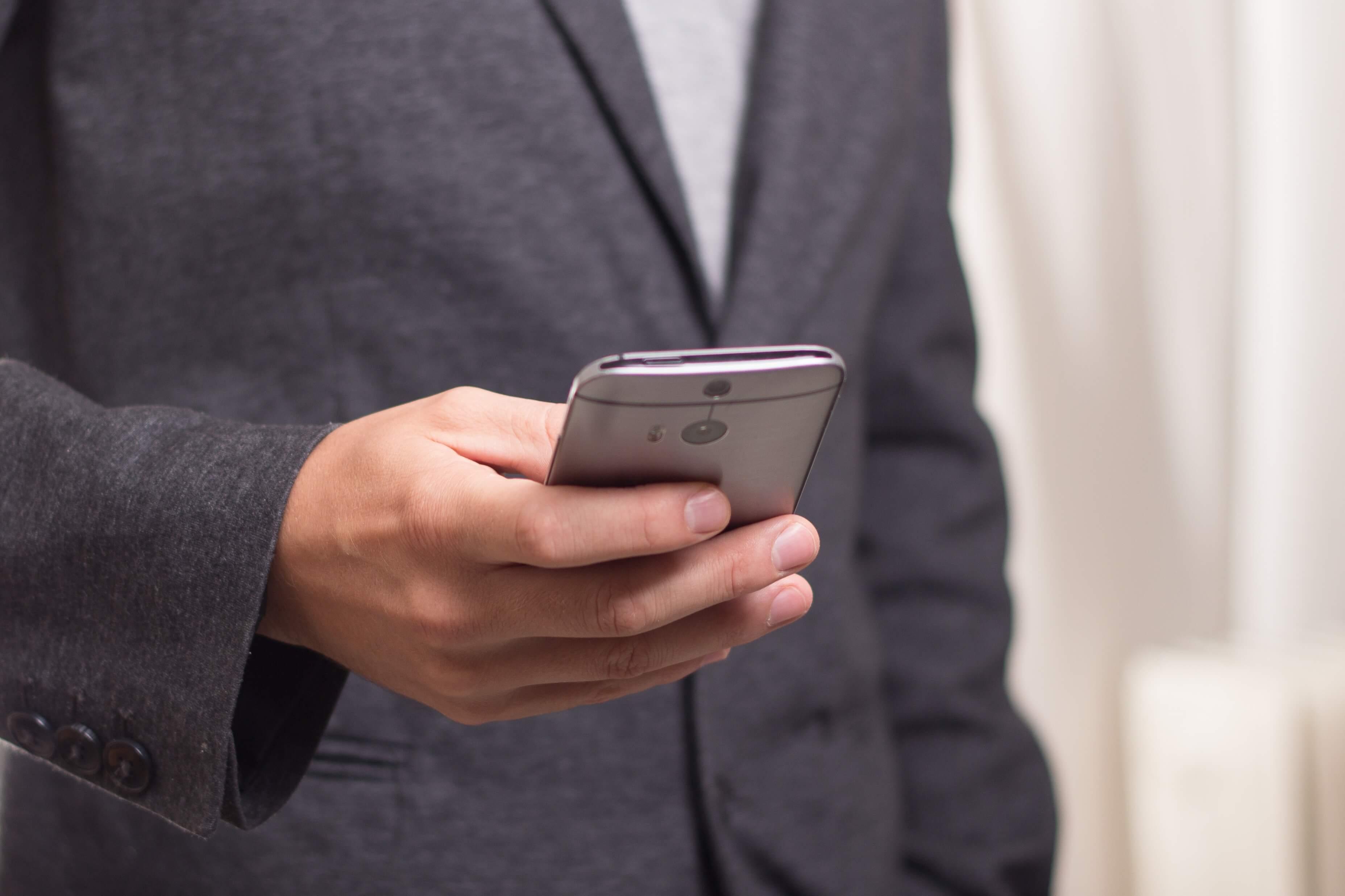 男性がスマートフォンをいじっている画像