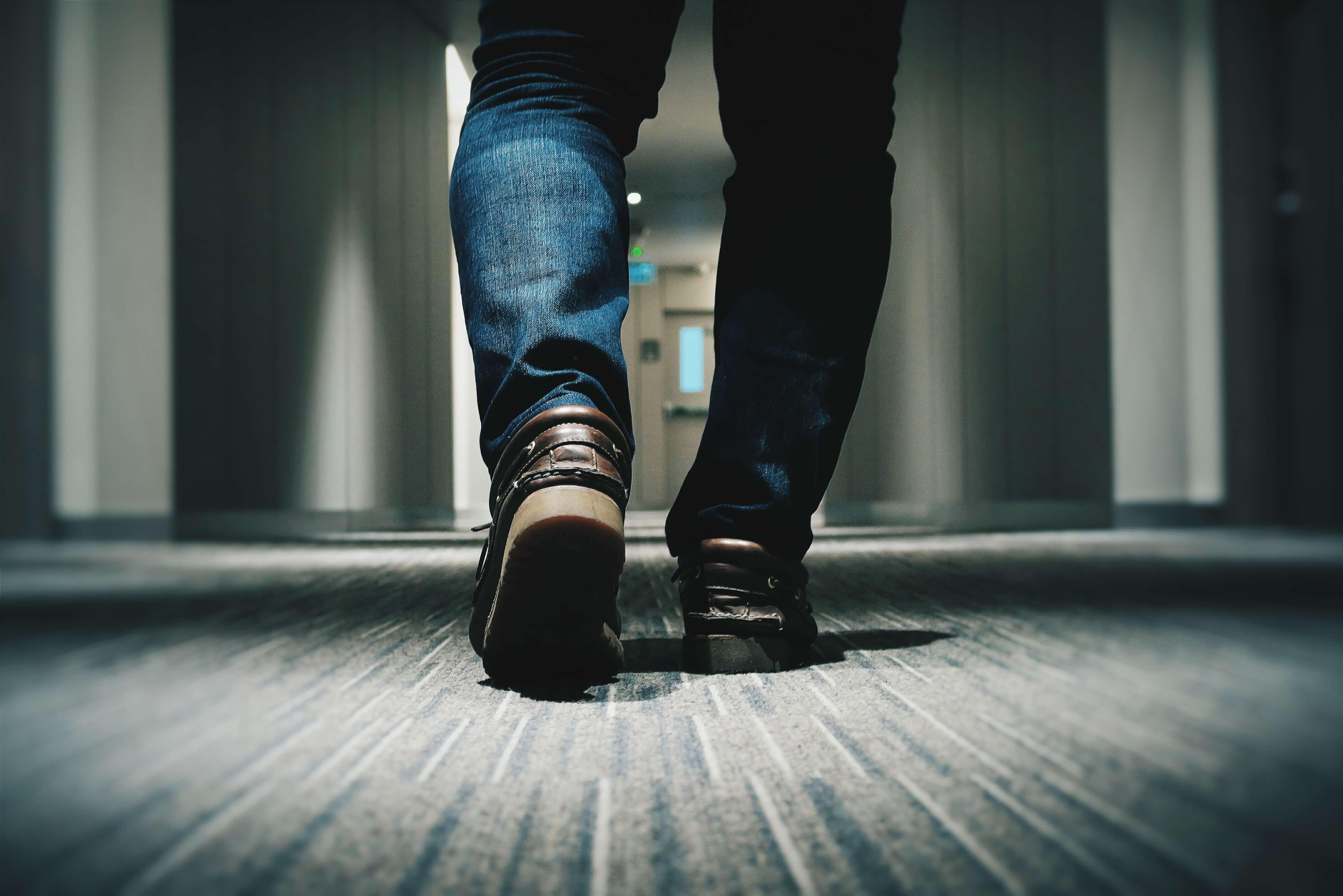 男性が歩く後ろ姿の足元の画像