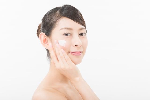 顔にクリームを塗る女性の画像