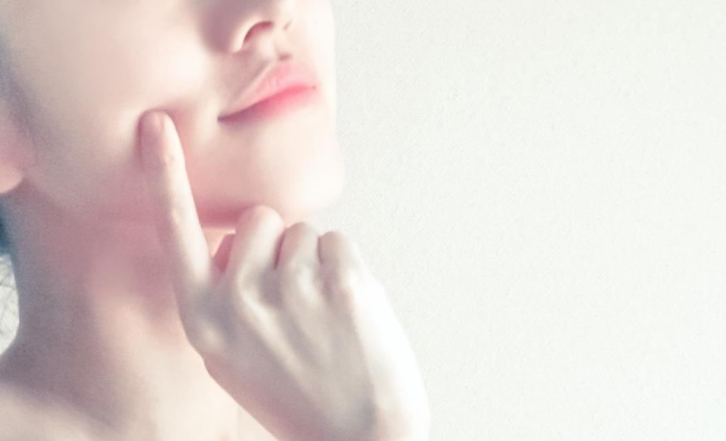 顔をさわる女性の画像