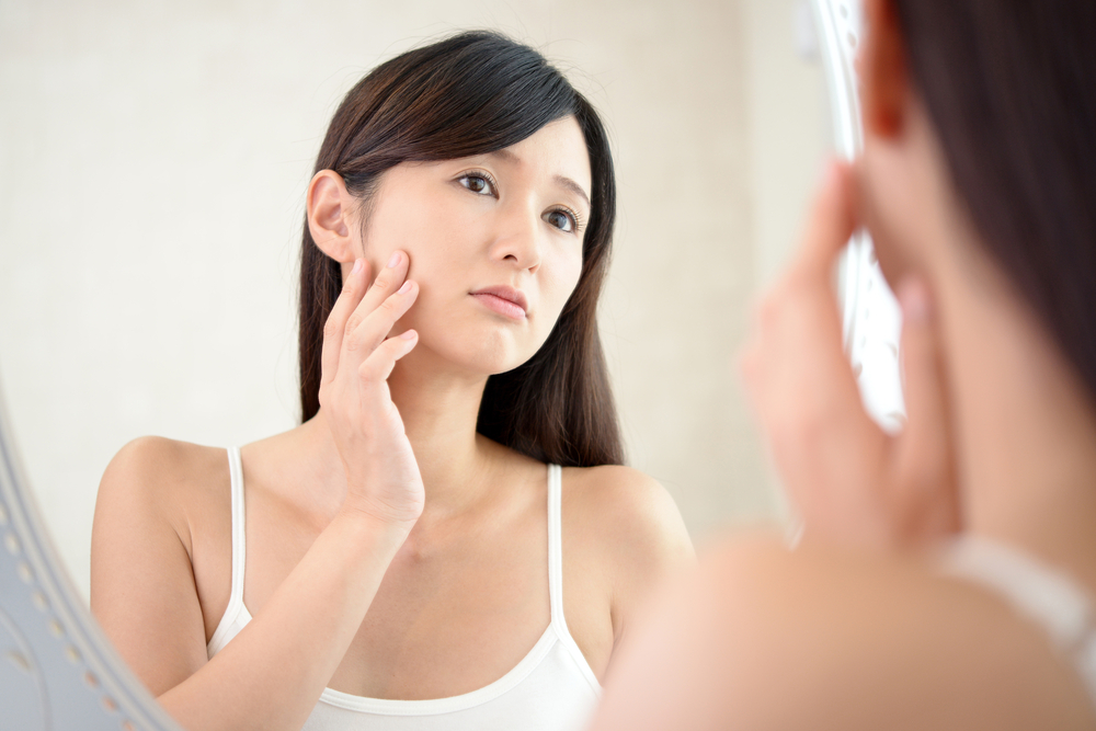鏡を見て不安げな女性の画像