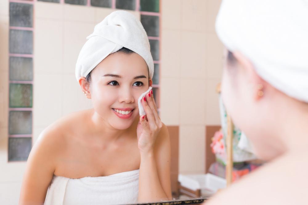 コットンで顔に化粧水をつけている画像