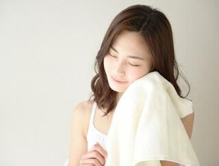 タオルで顔をぬぐう女性
