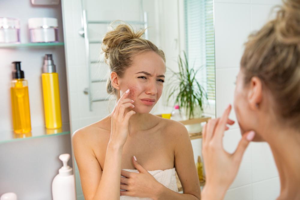 鏡の前で顔を見ている女性
