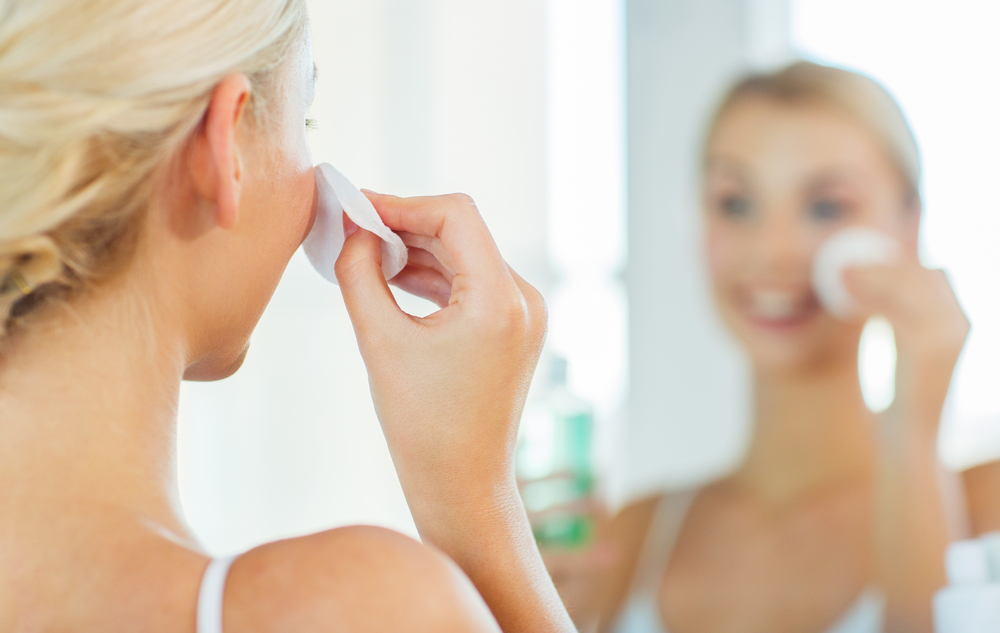 鏡の前でスキンケアをしている女性の画像